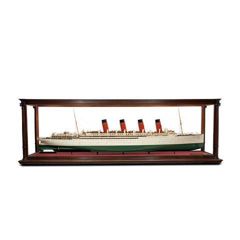 A ship  model in a glass case. It has four chimneys. All the details such as the windows, lifeboats and ropes are presented very well.