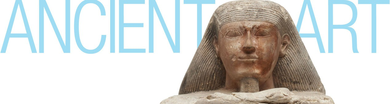 """A close view of A Priest of Hathor sculpture. The collection title """"Ancient Art"""" is behind it."""