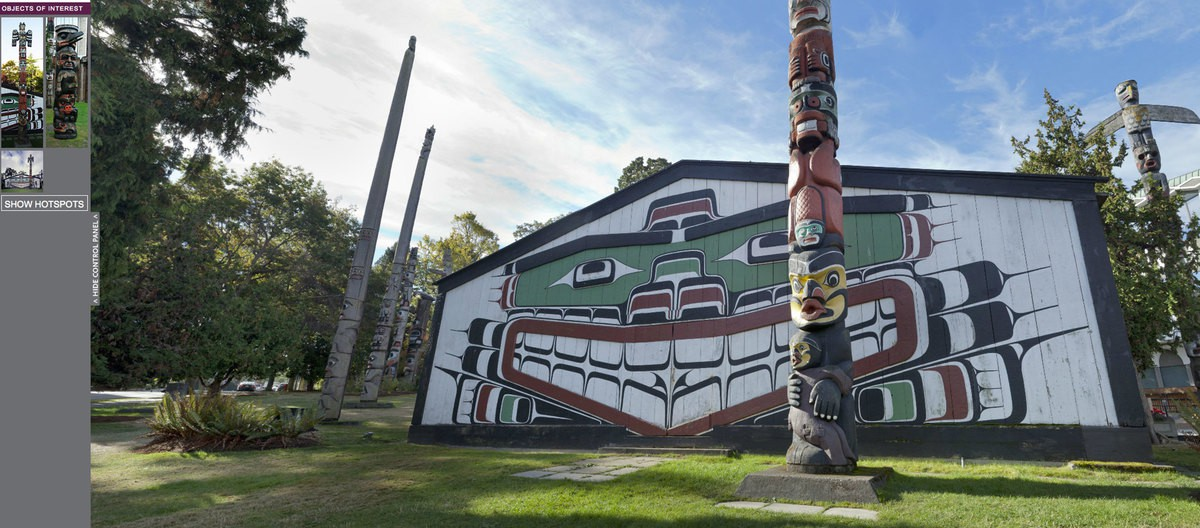 A big wooden house with mural is surround by several totem poles.