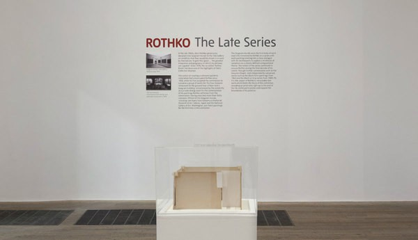 Three Rothko's black and grey patings are hanging on the wall in the gallery.