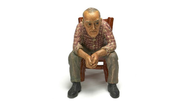 A close view of a clay sculpture made by Joe Fafard which is a man is sitting on a chiar with a serious facial expression. The website navigation sidebar is on his left side.
